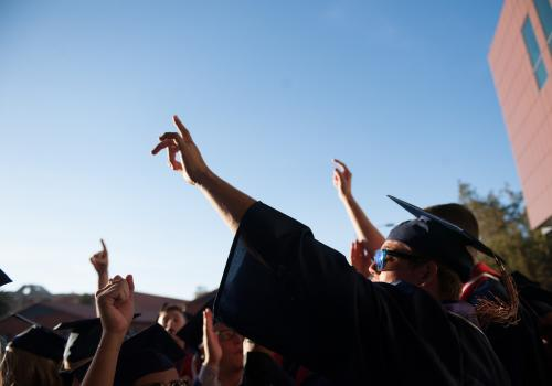 Graduates pointing in the air